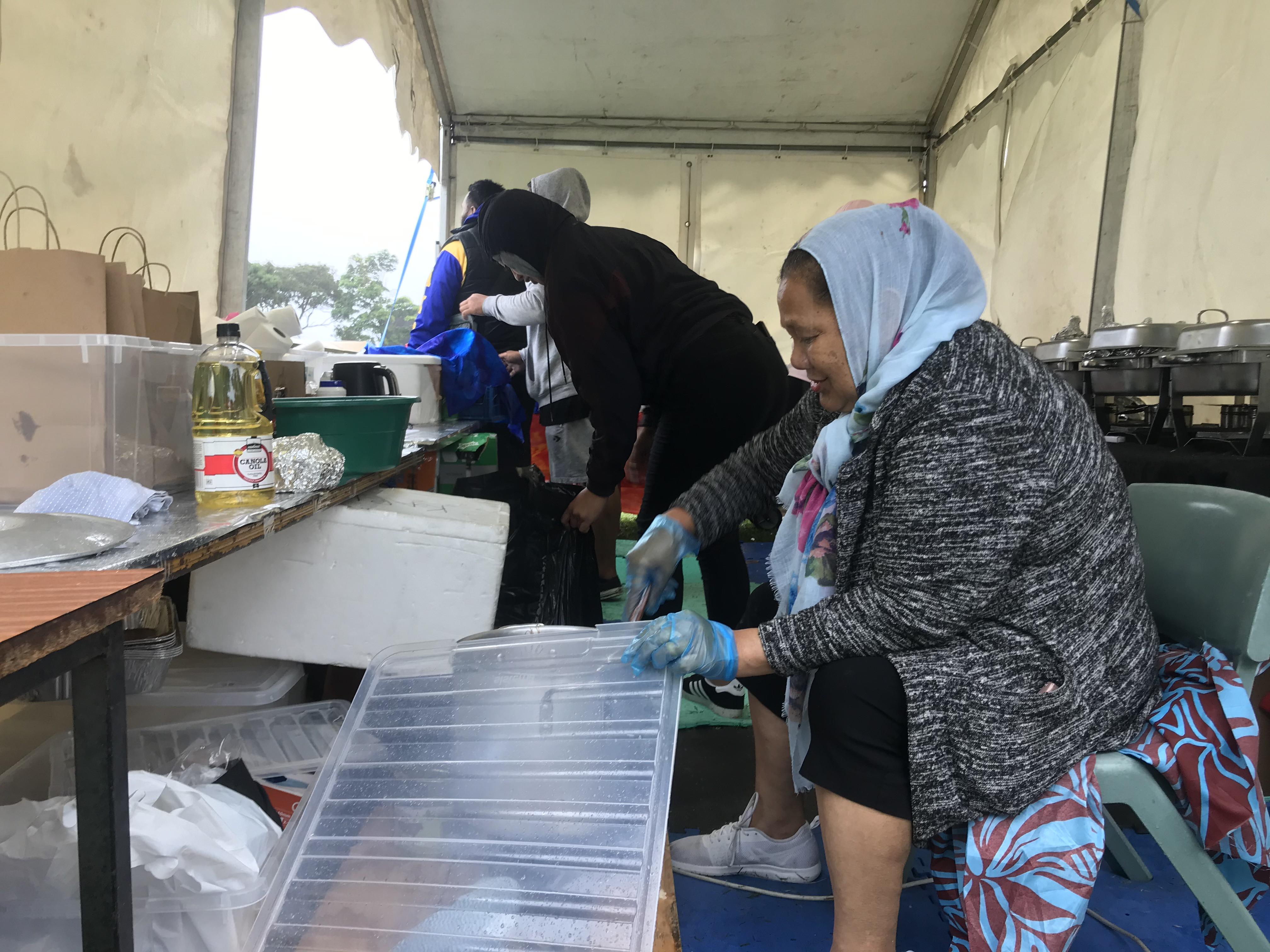 Michael Kapisi's (in background) family prepare their Niuean dishes for Pasifika festival attendees